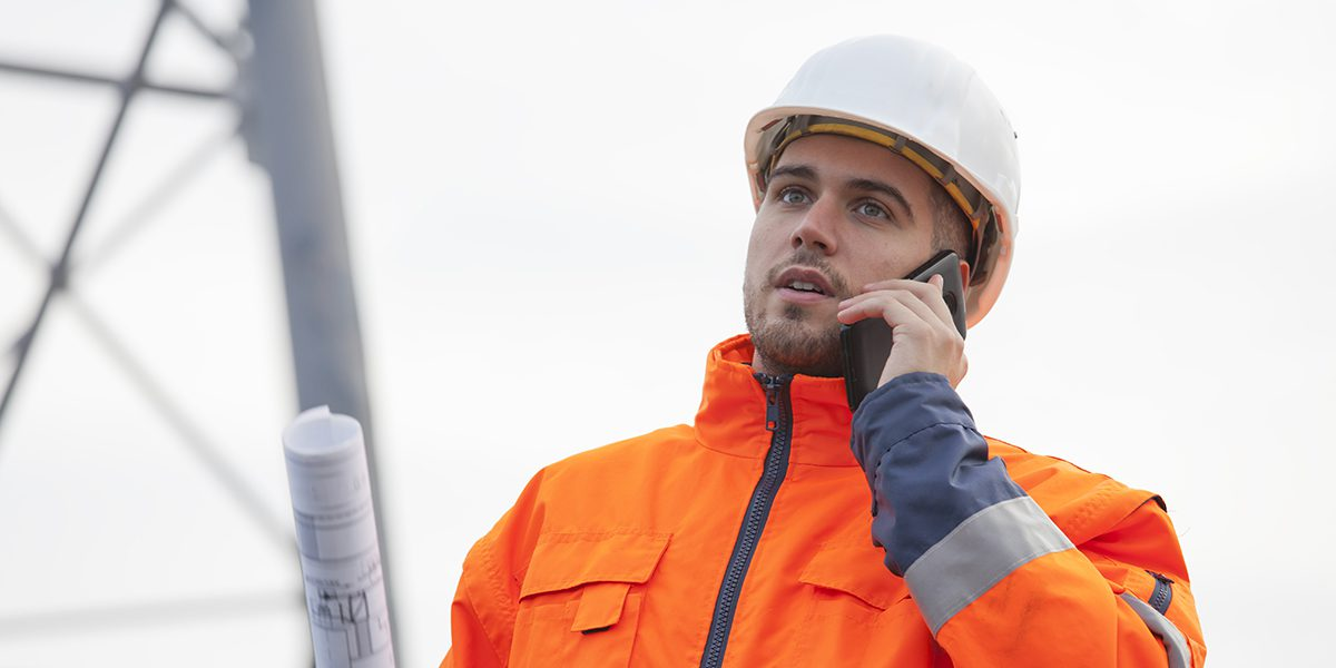 Young engineer or foreman talking on smart phone on a oil platform or construction site